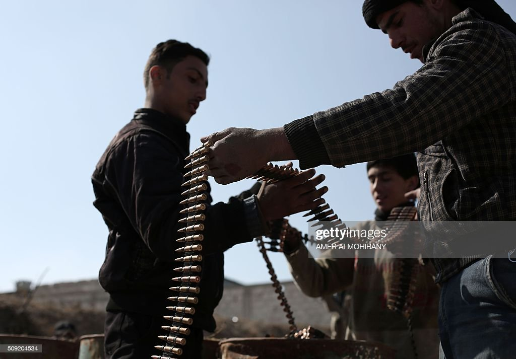 Opposition fighters check their ammunition belts in Tal al-Aswan in the area of the eastern Ghouta rebel bastion east of the Syrian capital, Damascus, during clashes with government forces on February 9, 2016. / AFP / AMER ALMOHIBANY