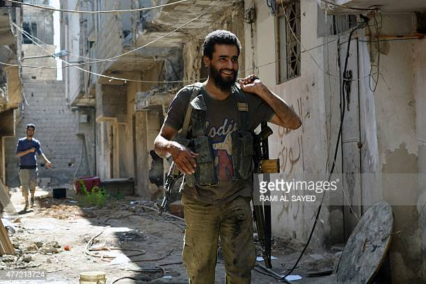 Opposition fighters belonging to the Islamist group Ansar alIslam and the Ahrar ashSham group walk on a street next to the front line that divides...