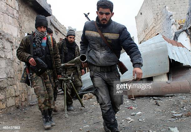 Opposition fighters carry a rocket launcher during clashes against government forces in the Sheikh Lutfi area west of the airport in the northern...