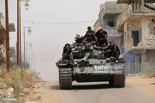 TOPSHOT Opposition fighters drive a tank in a rebelheld area of the southern Syrian city of Daraa during renewed clashes with regime loyalists on May...