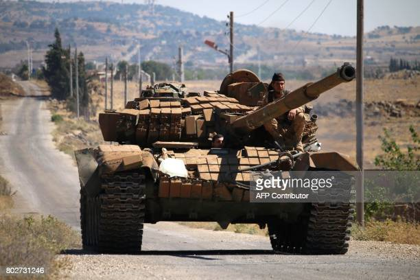 Opposition fighters drive a tank in Syria's southwestern Quneitra province on June 28 2017 during ongoing clashes with government forces for control...