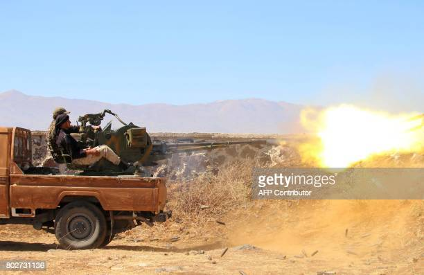 Opposition fighters fire a heavy machine gun during clashes with government forces for the control of the city of alBaath in Syria's southwestern...