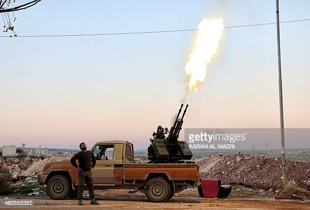 Opposition fighters fire a heavy machine gun towards government forces helicopters reportedly dropping barrel bombs near the northern Syrian city of...