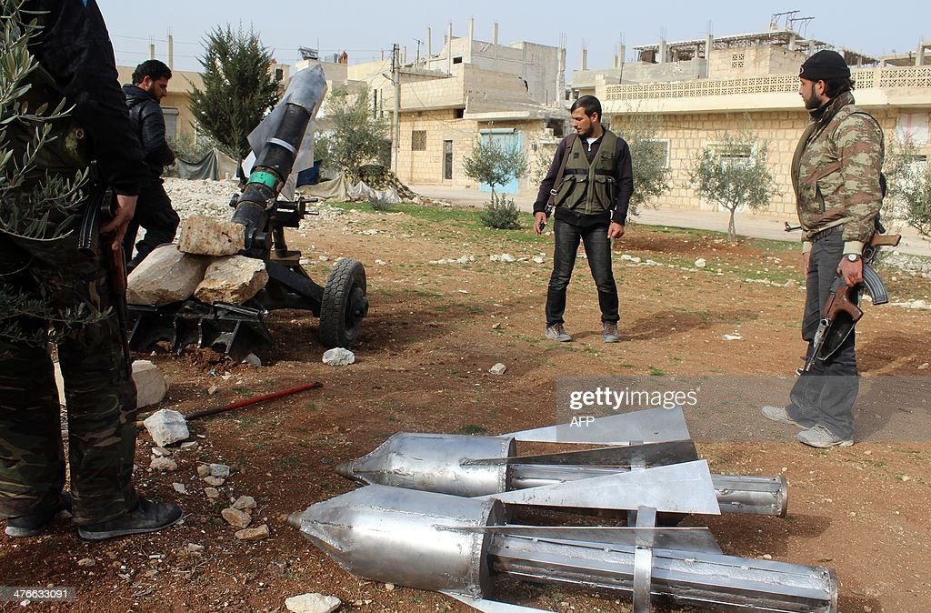 Opposition fighters load a homemade rocket launcher during clashes with government forces in the town of Khan Sheikhun, in Syria's Idlib province on March 2, 2014. More than 140,000 people have been killed in Syria's war, and millions more forced to flee their homes.