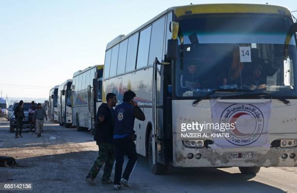 Opposition forces and Syrian civil defence volunteers known as the White Helmets welcome a convoy of buses transporting Syrians who were evacuated...