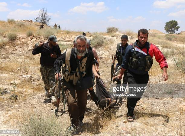 Opposition forces carry a wounded soldier after they captured him as they clash with Assad regime's forces in Daraa Syria on June 20 2017
