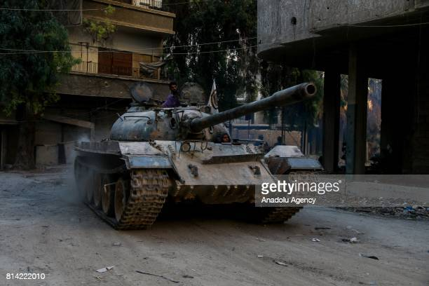 Opposition forces drive a tank during a clash after Assad Regime's forces hit a deconflict zone of opposition controlled Jobar neighborhood in...
