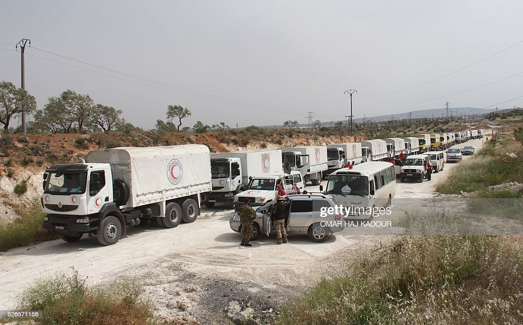 Opposition forces (R) escort a convoy of aid vehicles heading to the government-held Shiite towns of Fuaa and Kafraya in Syria's northwestern Idlib province, on April 30, 2016. Humanitarian convoys carrying food and medicine entered the besieged rebel-held towns of Madaya and Zabadani, northwest of Damascus, the Red Cross said. At the same time, trucks entered the besieged government-held towns of Fuaa and Kafraya, southwest of Aleppo. / AFP / Omar haj kadour