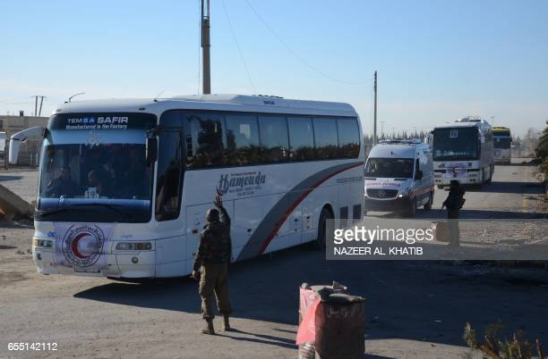 Opposition forces welcome a convoy of buses transporting Syrians who were evacuated from Waer the last oppositionheld district of Homs under a...