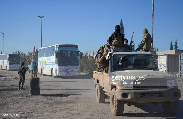 Opposition forces welcome buses transporting Syrians who were evacuated from Waer the last oppositionheld district of Homs under a controversial...