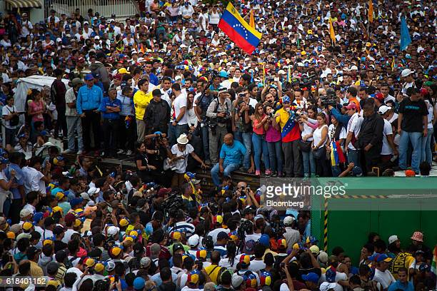 Opposition governor Henrique Capriles speaks on a microphone as demonstrators and press listen during a protest against the suspended recall...