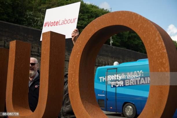 Opposition Labour Party activists hold a sign saying Vote Labour near to the Conservative Party campaign bus ahead of the launch of the Conservative...