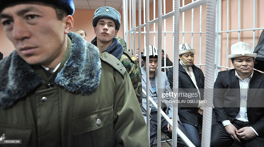 Opposition lawmakers, including the head of the nationalist Ata-Zhurt party Kamchybek Tashiev (L) and his two fellow lawmakers Sadyr Zhaparov (C) and Talant Mamytov (R) sit inside the defendants cage in a court in the Kyrgyzstan's capital Bishkek on January 25, 2013. during the lawmakers' trial. Tashiev was arrested last year along with two other lawmakers over their role in a protest on the previous day demanding the nationalisation of the Canadian-owned Kumtor mine.