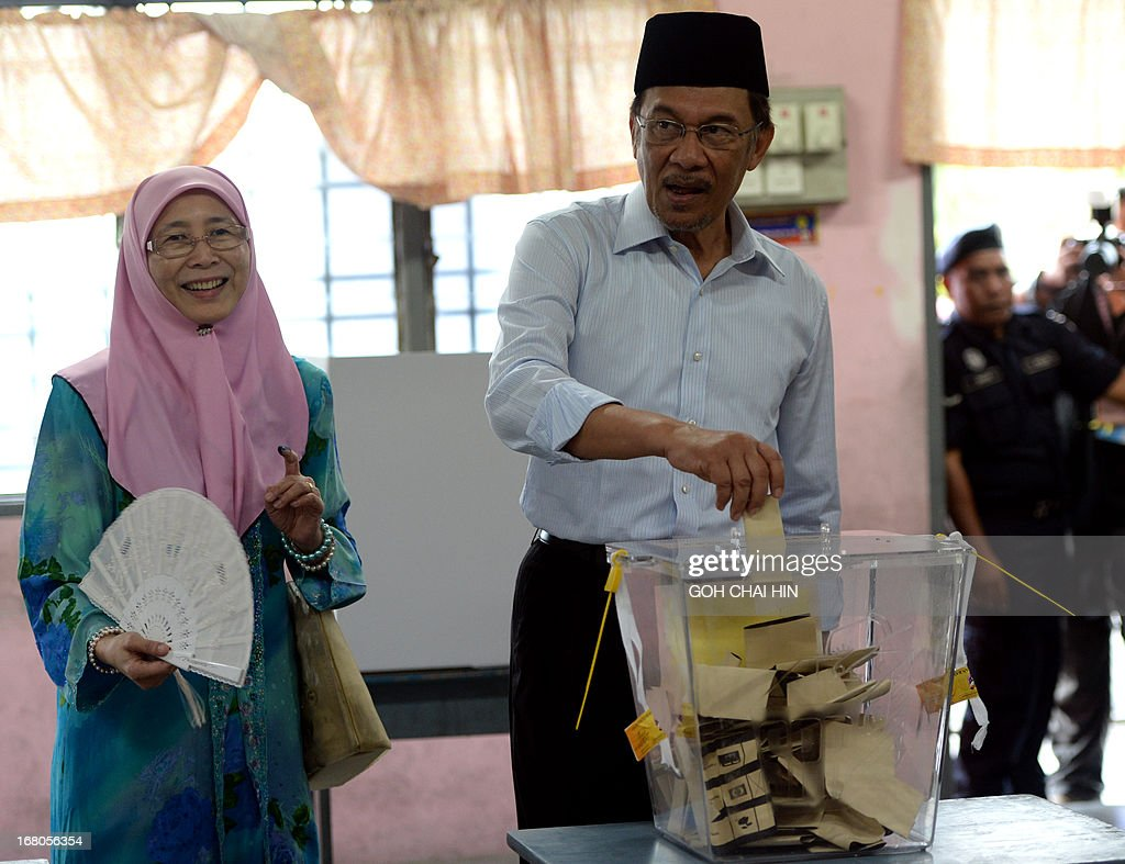 Opposition leader Anwar Ibrahim accompanied by his wife Wan Azizah (L), casts his vote at a polling station in Permatang Pauh, Penang on May 5, 2013. Malaysians voted in their first election in history with a change of government at stake, as a decades-old regime battles to hold off a rising opposition pledging sweeping reform. AFP PHOTO/GOH CHAI HIN