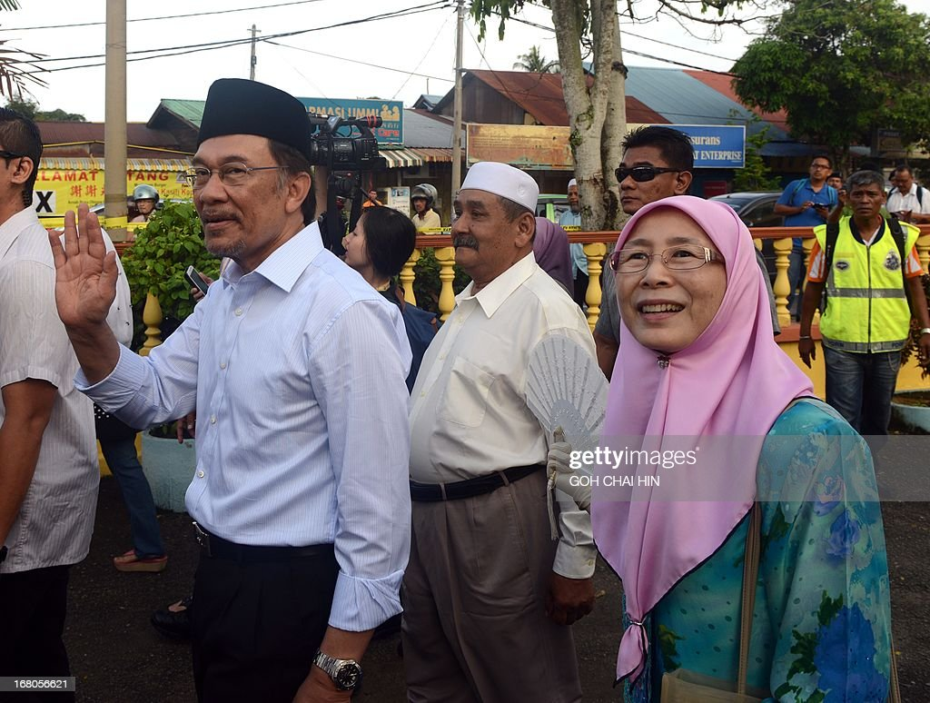 Opposition leader Anwar Ibrahim (L) and his wife Wan Azizah leave the polling station after casting their their votes at a polling station in Permatang Pauh, Penang on May 5, 2013. Malaysians voted in their first election in history with a change of government at stake, as a decades-old regime battles to hold off a rising opposition pledging sweeping reform.