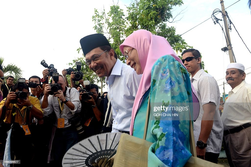 Opposition leader Anwar Ibrahim and his wife Wan Azizah leave the polling station after casting their their votes at a polling station in Permatang Pauh, Penang on May 5, 2013. Malaysians voted in their first election in history with a change of government at stake, as a decades-old regime battles to hold off a rising opposition pledging sweeping reform.