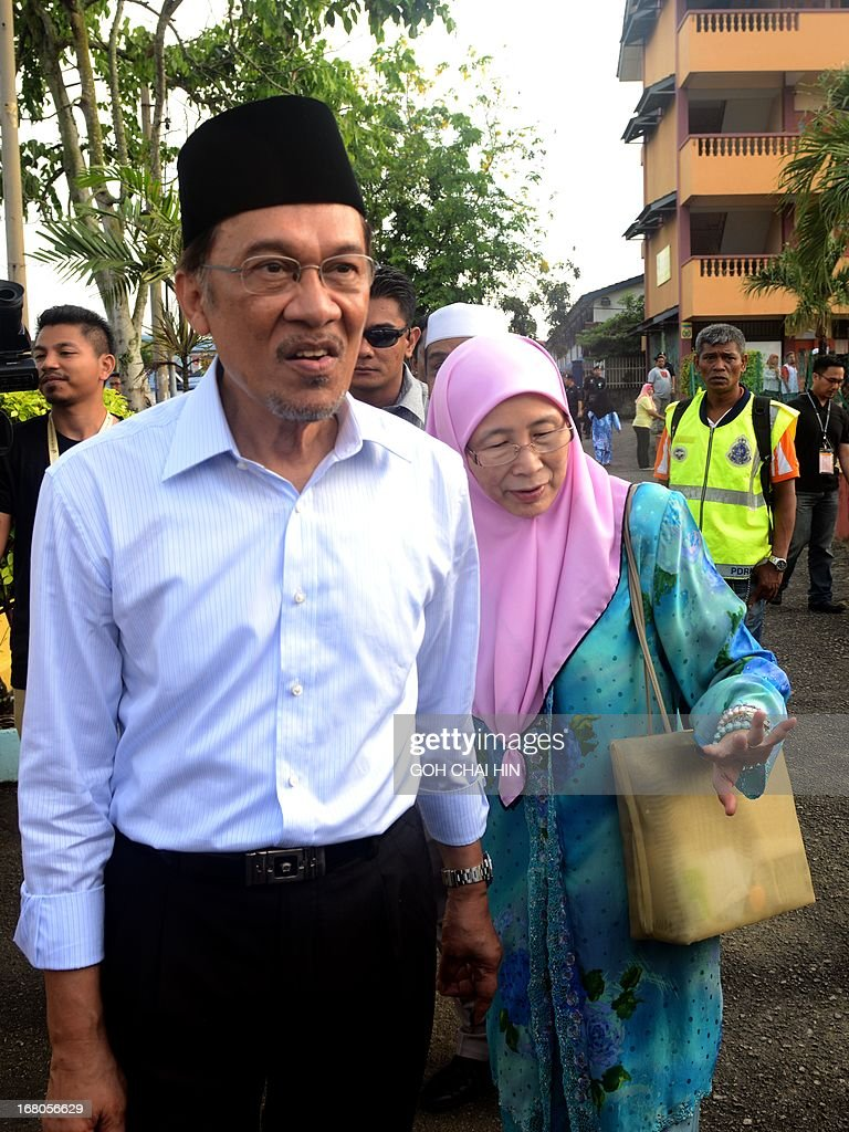 Opposition leader Anwar Ibrahim (L) and his wife Wan Azizah leave the polling station after casting their their votes at a polling station in Permatang Pauh, Penang on May 5, 2013. Malaysians voted in their first election in history with a change of government at stake, as a decades-old regime battles to hold off a rising opposition pledging sweeping reform. AFP PHOTO/GOH CHAI HIN
