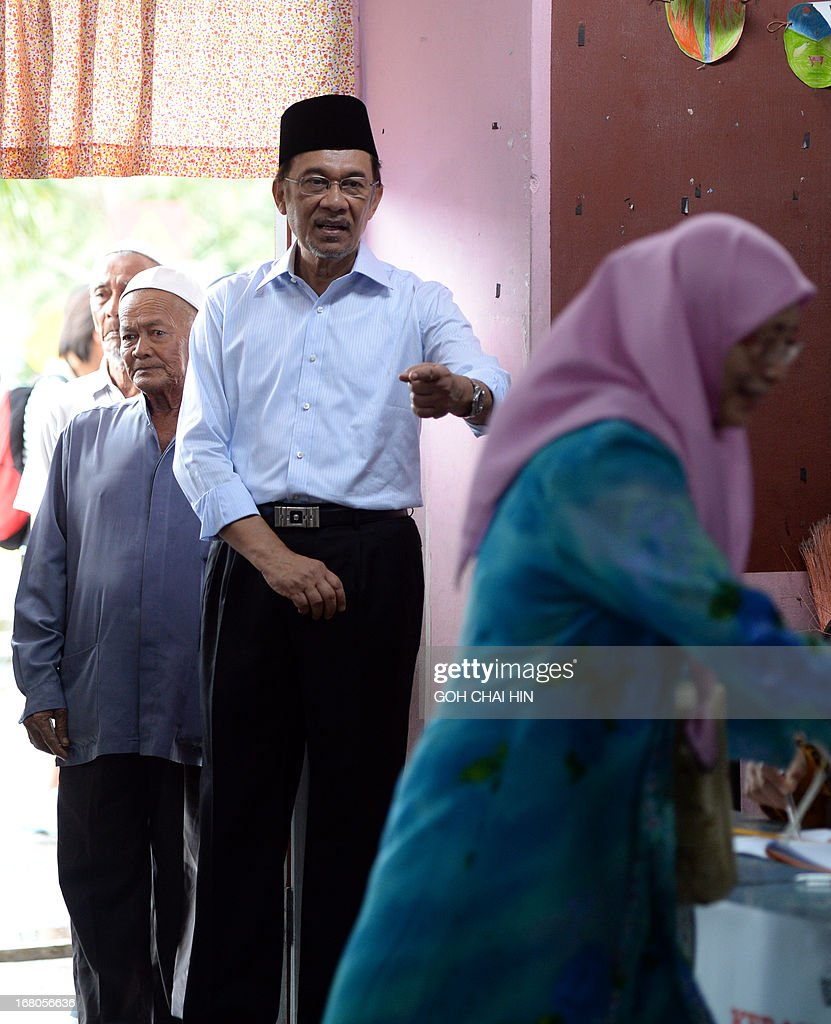 Opposition leader Anwar Ibrahim (C) talks to his wife Wan Azizah (R) as she gets her finger mark with the idelible ink at a polling station in Permatang Pauh, Penang on May 5, 2013. Malaysians voted in their first election in history with a change of government at stake, as a decades-old regime battles to hold off a rising opposition pledging sweeping reform.