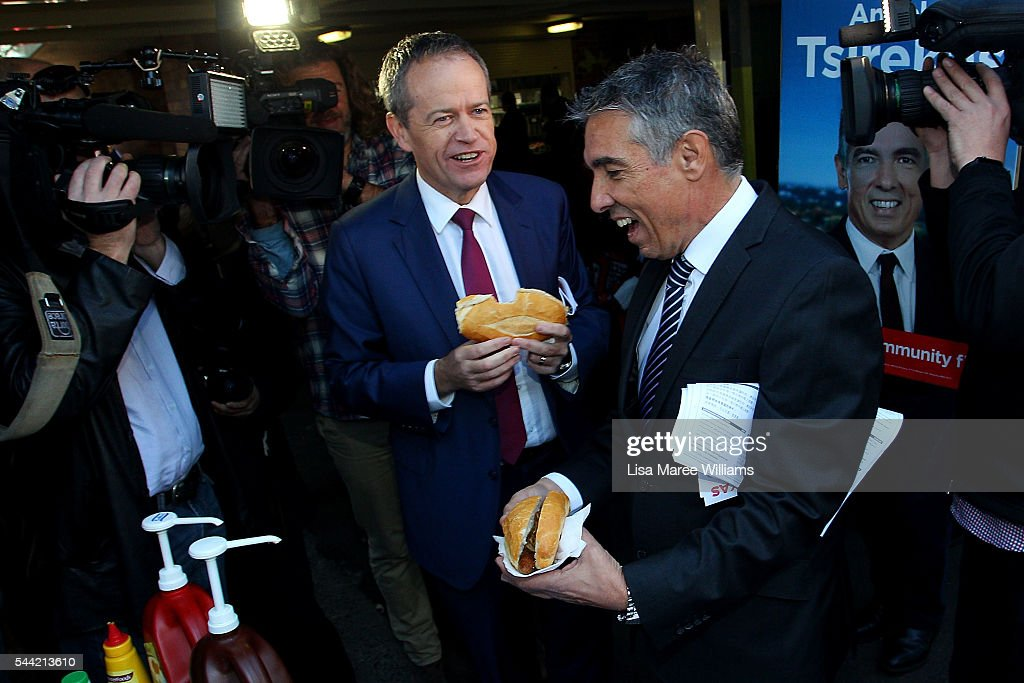 Opposition Leader, Australian Labor Party Bill Shorten enjoys a sausage bread roll during a visit to a polling booth at Strathfield North Public School on July 2, 2016 in Sydney, Australia. After 8 official weeks of campaigning, Labor party leader, Bill Shorten will cast his vote and await results as Australians head to the polls to elect the 45th Parliament.