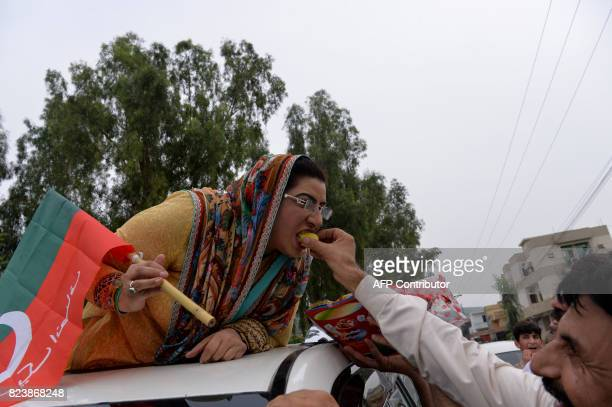 Opposition leader Firdous Ashiq Awan of Imran Khan's Pakistan TehreekiInsaf party eats sweets while celebrating the Supreme Court decision against...