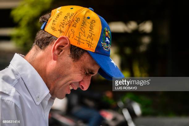 Opposition leader Henrique Capriles gestures as he suffers from the effects of tear gas during clashes between antigovernment protesters and the riot...