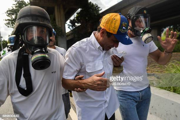 Opposition leader Henrique Capriles is assisted as he suffers from the effects of tear gas during clashes between antigovernment protesters and the...