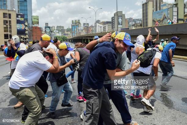 TOPSHOT Opposition leader Henrique Capriles looks for refuge under a bridge as police throw tear gas during a rally against Venezuelan President...
