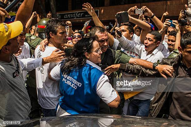 Opposition leader Leopoldo Lopez center left is led to an armored vehicle by police during an antigovernment demonstration in Caracas Venezuela on...