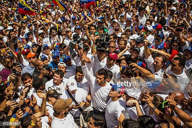 Opposition leader Leopoldo Lopez front center raises his hand while surrounded by protesters during an antigovernment demonstration in Caracas...