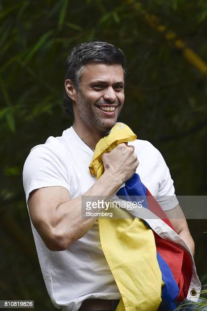 Opposition leader Leopoldo Lopez holds a Venezuelan flag as he arrives home after being released from jail in Caracas Venezuela on Saturday July 8...