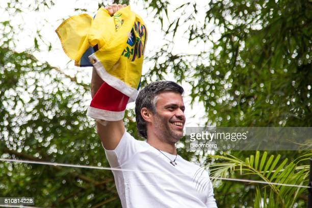 Opposition leader Leopoldo Lopez waves a Venezuelan flag as he arrives home after being released from jail in Caracas Venezuela on Saturday July 8...