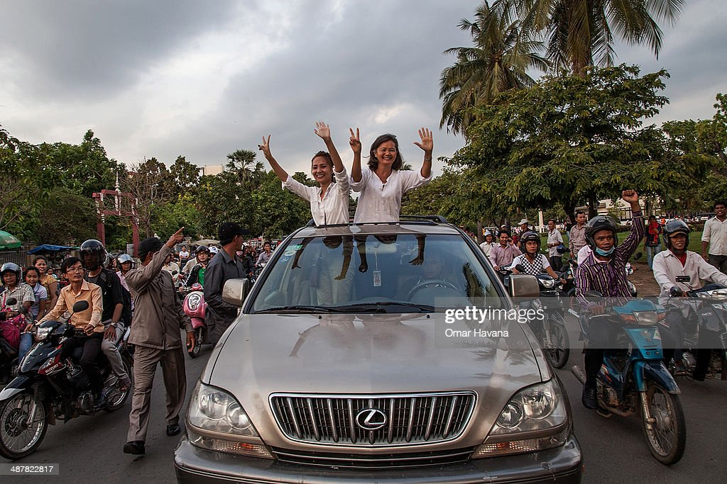 Opposition leader Mu Sochua and CNRP representative Kem Monovithya greet supporters during the first day of local election campaigning on May 2, 2014 in Phnom Penh, Cambodia. Thousands of military police and municipal security guards have been deployed in Phnom Penh on the first day of campaigning for upcoming local elections in Cambodia. The opposition Cambodian National Rescue Party was blocked from entering Freedom Park, which was the opposition's main rallying point during last year's national elections, and at least three people were injured, including CNRP parliamentarian Chamroeun Nhay as he was trying to access the park. Despite the government's recent ban on all public campaigning ahead of the upcoming local elections, the opposition party rallied in the streets of Phnom Penh for the first day of the campaign in defiance of the ban.