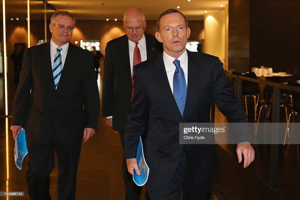 Opposition Leader <a gi-track='captionPersonalityLinkClicked' href=/galleries/search?phrase=Tony+Abbott&family=editorial&specificpeople=220956 ng-click='$event.stopPropagation()'>Tony Abbott</a> Leaves the media conference after unveiling the Coalition Border Protection Policy with Shadow Minister for Immigration Scott Morrison and retired Australian Army Major-General, Jim Molan at the Hilton Hotel on July 25, 2013 in Brisbane, Australia. Abbott announced that if elected to government at the upcoming election the establishment of a AUD$10m taskforce to tackle people smugglers, headed by a military commander, and stated that asylum seekers making their way to Australia a 'national emergency.'