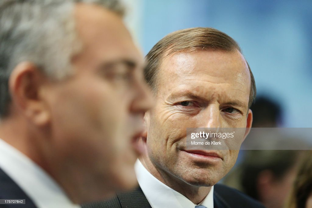 Opposition Leader <a gi-track='captionPersonalityLinkClicked' href=/galleries/search?phrase=Tony+Abbott&family=editorial&specificpeople=220956 ng-click='$event.stopPropagation()'>Tony Abbott</a> listens to Joe Hockey speak to the media at a press conference at the Bickfords facility in Salisbury South, on August 7, 2013 in Adelaide, Australia. Mr Abbott is campaigning in Adelaide today announcing a proposed 1.5% tax rate cut for business if elected in the upcoming 2013 Federal Election on September 7th.