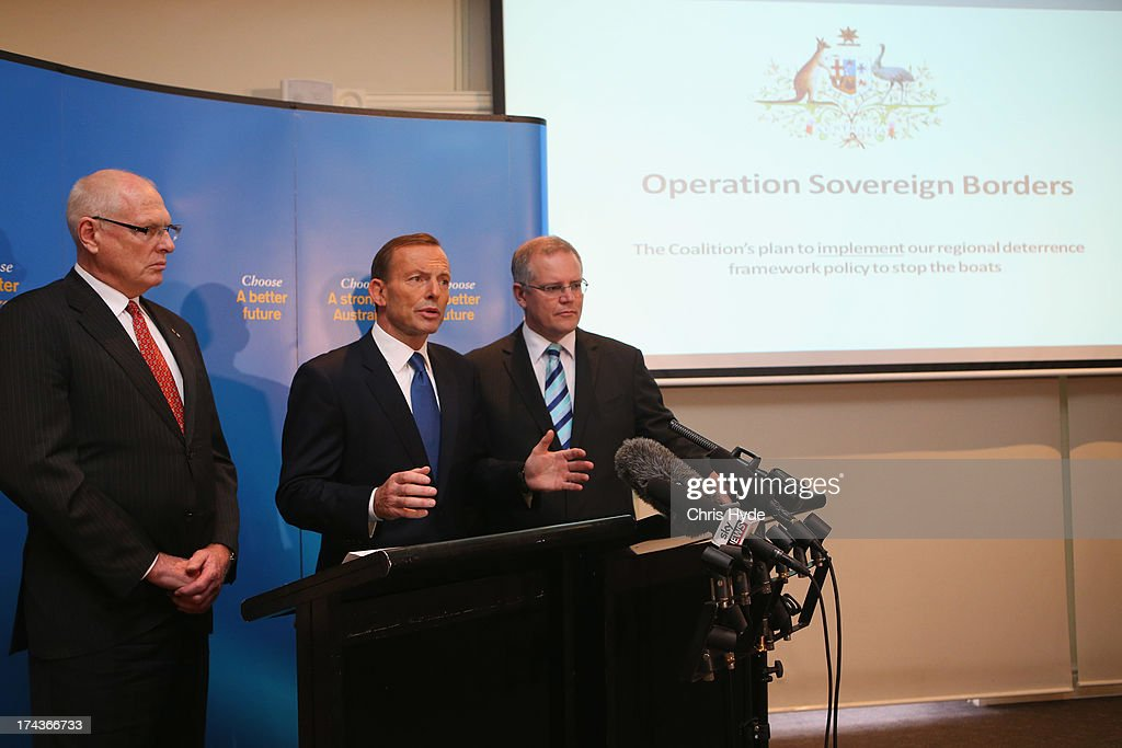 Opposition Leader <a gi-track='captionPersonalityLinkClicked' href=/galleries/search?phrase=Tony+Abbott&family=editorial&specificpeople=220956 ng-click='$event.stopPropagation()'>Tony Abbott</a> unveils the Coalition Border Protection Policy with (L) retired Australian Army Major-General, Jim Molan and Shadow Minister for Immigration Scott Morrison at the Hilton Hotel on July 25, 2013 in Brisbane, Australia. Abbott announced that if elected to government at the upcoming election the establishment of a AUD$10m taskforce to tackle people smugglers, headed by a military commander, and stated that asylum seekers making their way to Australia a 'national emergency.'