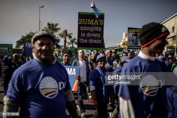 Opposition parties members hold signs as they march to support a Motion of no Confidence against South African president Jacob Zuma to be debated in...