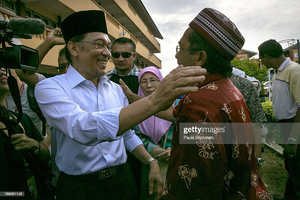 Opposition party leader Anwar Ibrahim greets a supporter after voting May 5, 2013 in Penanti, Malaysia. Millions of Malaysians cast their vote on Sunday in one of the most tightly contested Malaysian election since independence in 1957. The opposition coalition, Pakatan Rakyat (People's Alliance), led by former deputy prime minister Anwar Ibrahim is seeking to gain power on a national level against the ruling party Barisan Nasional.