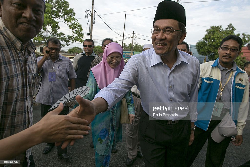 Opposition party leader <a gi-track='captionPersonalityLinkClicked' href=/galleries/search?phrase=Anwar+Ibrahim&family=editorial&specificpeople=600601 ng-click='$event.stopPropagation()'>Anwar Ibrahim</a> greets a supporter before casting his vote May 5, 2013 in Penanti, Malaysia. Millions of Malaysians cast their vote on Sunday in one of the most tightly contested Malaysian election since independence in 1957. The opposition coalition, Pakatan Rakyat (People's Alliance), led by former deputy prime minister <a gi-track='captionPersonalityLinkClicked' href=/galleries/search?phrase=Anwar+Ibrahim&family=editorial&specificpeople=600601 ng-click='$event.stopPropagation()'>Anwar Ibrahim</a> is seeking to gain power on a national level against the ruling party Barisan Nasional.