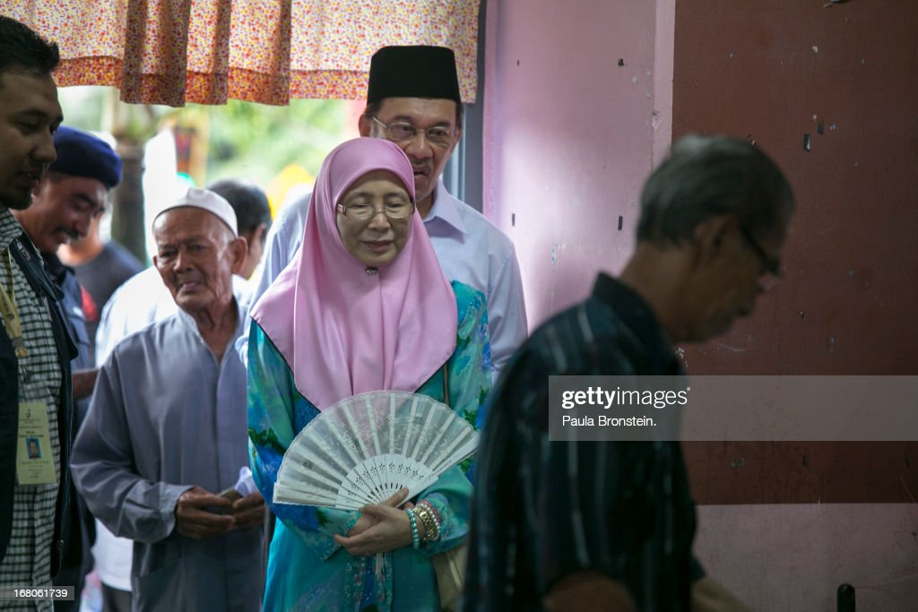 Opposition party leader Anwar Ibrahim stands in line to vote along side his wife Dr, Wan Nur Azizah May 5, 2013 in Penanti, Malaysia. Millions of Malaysians cast their vote on Sunday in one of the most tightly contested Malaysian election since independence in 1957. The opposition coalition, Pakatan Rakyat (People's Alliance), led by former deputy prime minister Anwar Ibrahim is seeking to gain power on a national level against the ruling party Barisan Nasional.