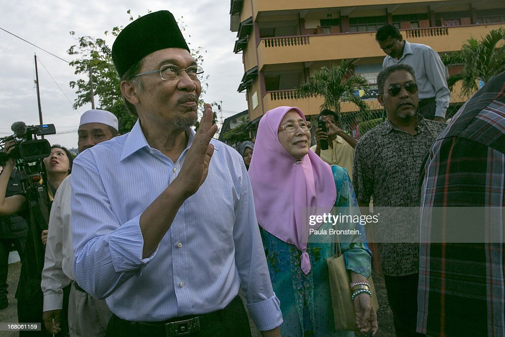 Opposition party leader Anwar Ibrahim walks along side his wife Dr, Wan Nur Azizah after casting his vote May 5, 2013 in Penanti, Malaysia. Millions of Malaysians cast their vote on Sunday in one of the most tightly contested Malaysian election since independence in 1957. The opposition coalition, Pakatan Rakyat (People's Alliance), led by former deputy prime minister Anwar Ibrahim is seeking to gain power on a national level against the ruling party Barisan Nasional.