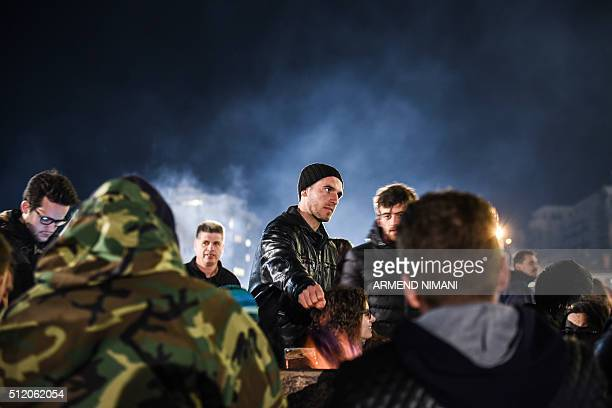 Opposition party supporters keep warm by a fire as they gather in front of Kosovo's government building in Pristina on February 24 to demand the...