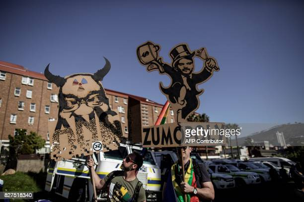 Opposition party's members shows signs mocking South African President Jacob Zuma during a march to support a Motion of no Confidence against Zuma to...