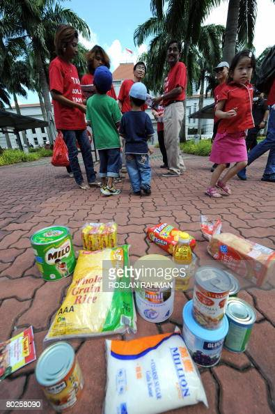 Opposition Singapore Democratic Party members and their children gather to protest against the prices hike with provision goods laid infront of the...