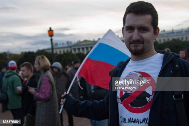 A opposition supporter seen holding the russian flag while participating in an unauthorized rally The President of Russia Vladimir Putin celebrated...