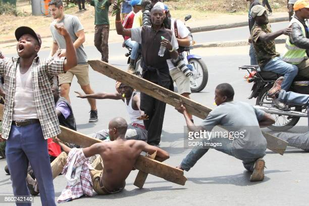 Opposition supporters are seen holding wood sticks on the streets of Nairobi during a protest in favor of their presidential candidate Raila Odinga...