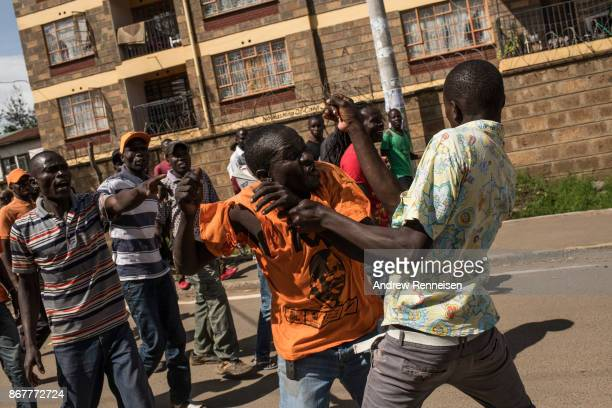 Opposition supporters beat a fellow supporter who threw a rock at a car as they marched down Ngong Road on October 29 2017 in Nairobi Kenya Tensions...