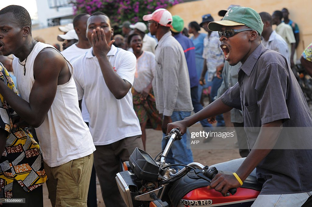 Opposition supporters follow police investigators conducting a search at the home of opposition leader Jean-Pierre Fabre in Lome. Opposition supporters gathered on March 12 outside the gates of the Gendarmerie Nationale in Lome after opposition leaders Fabre and Abass Kaboua were called in for questioning in relation with the January fires that destroyed the Grande Marches in Lome and Kara. AFP PHOTO / Daniel Hayduk