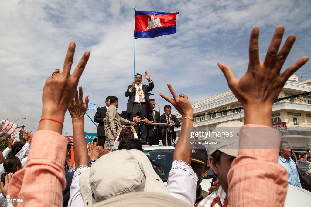 Opposition supporters greet Cambodia National Rescue Party President Sam Rainsy with a number seven which referred to the party in the last national...