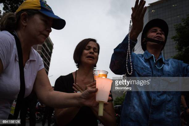 Opposition supporters hold candles and rosary beads while praying during a vigil in honor of 17 yearold protester Neomar Lander who died during a...