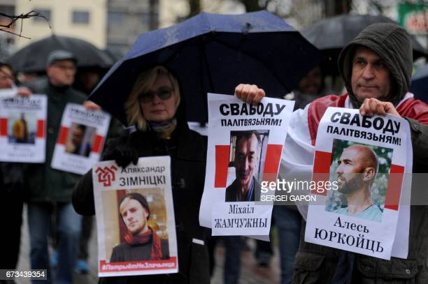 Opposition supporters hold portraits of detained activists as they take part in a rally in Minsk on April 26 to commemorate the victims of the...